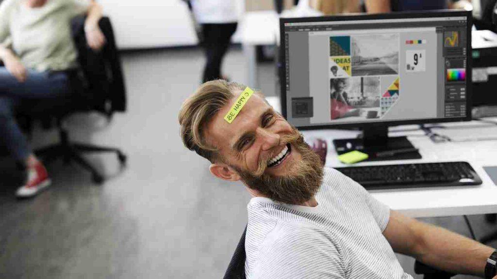"""Homem sorrindo com etiqueta colada na testa dizendo """"be happy""""."""