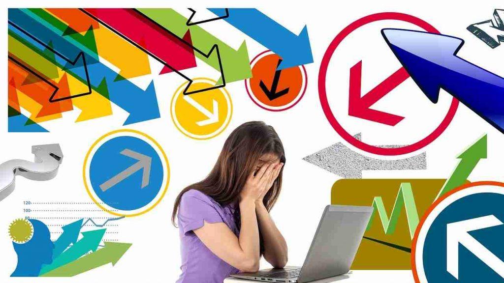 Mulher sentada frente a um computador tapando a cara com as mãos e numerosas setas desenhadas à sua volta, apontando em diversas direcções.