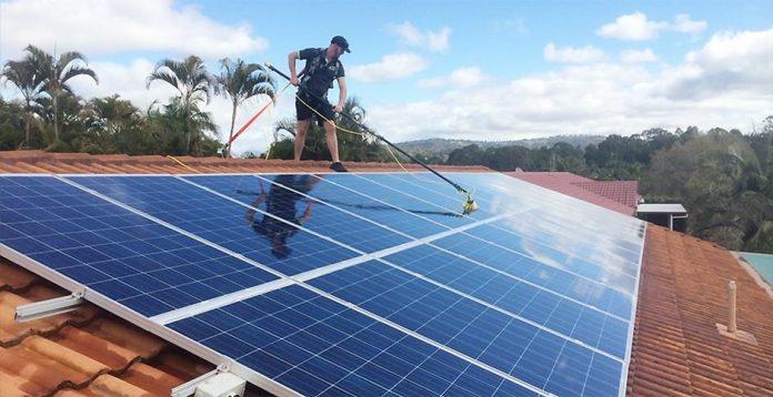 homem lavando painéis solares num telhado