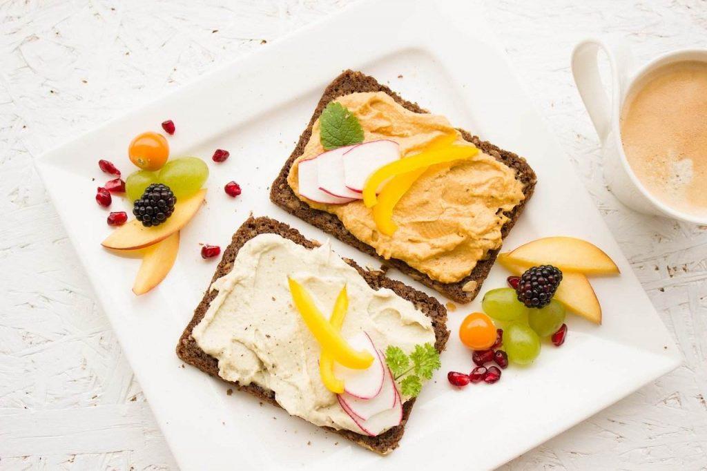 fatias de pão barradas com creme vegetal e com frutas e legumes