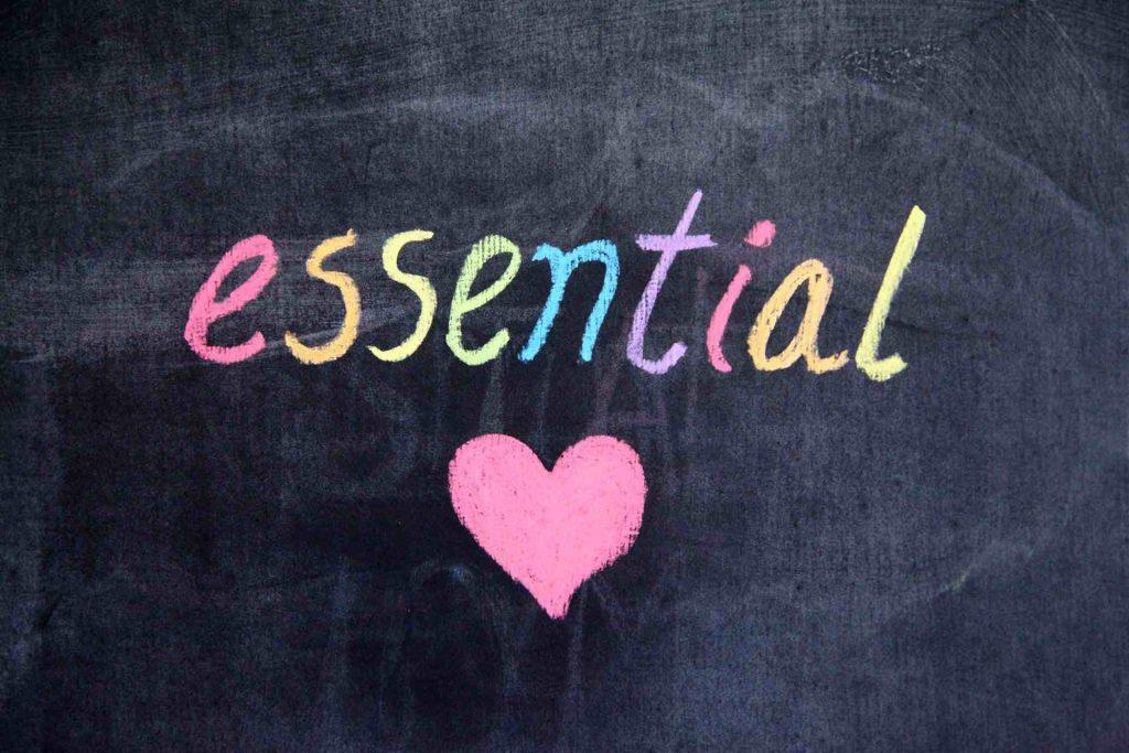 """Palavra """"essential"""" escrita a giz colorido e com um coração desenhado"""
