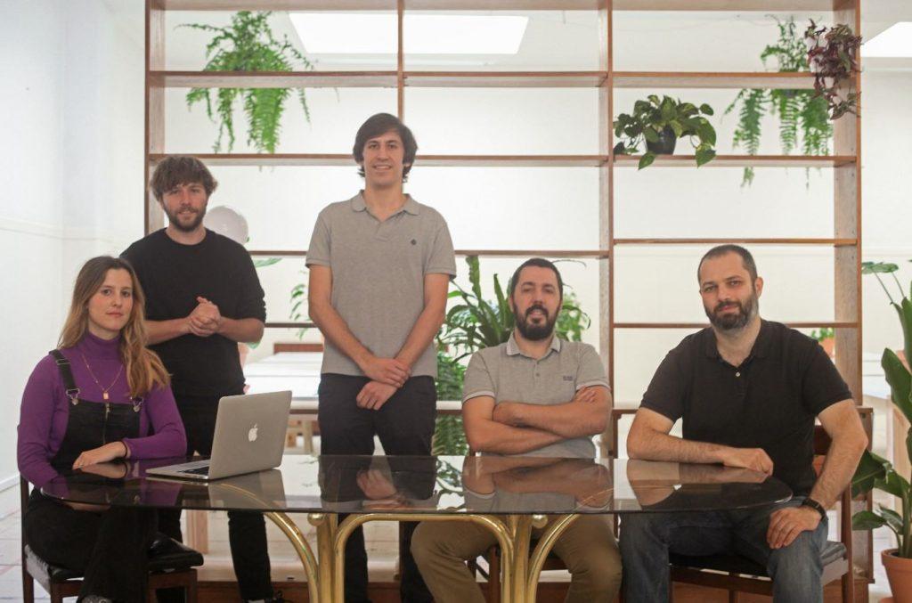 grupo de pessoas da equipa da BUK posando para a fotografia em volta de uma mesa, frente a uma estante com plantas.
