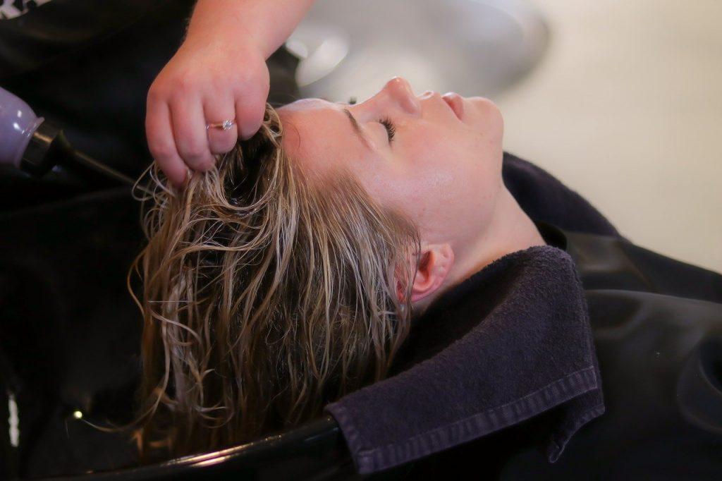 mulher secando cabelo de outra mulher em salão de beleza