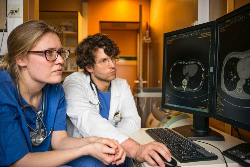 médicos observando tomografia num computador