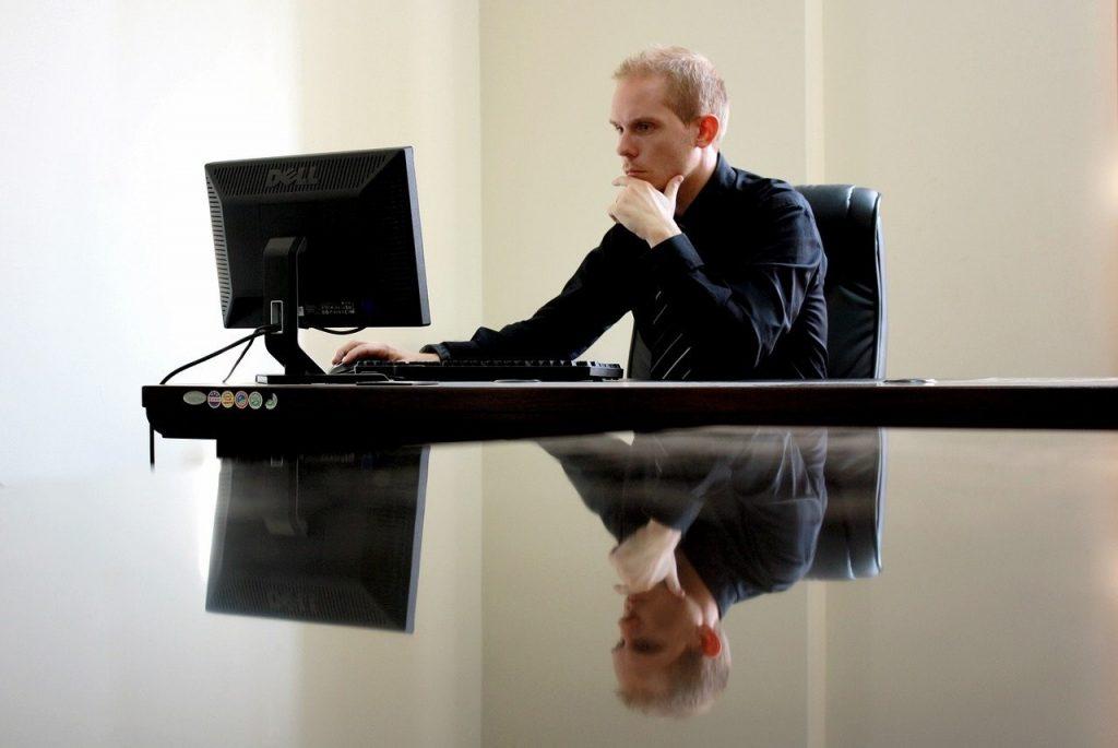 homem trabalhado num computador, com o seu reflexo espelhado no tampo da secretária