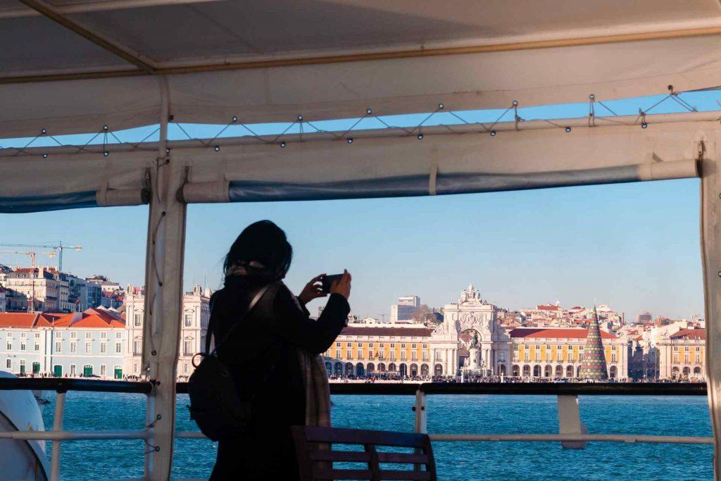Mulher na coberta de um navio, fotografando a Baixa de Lisboa.