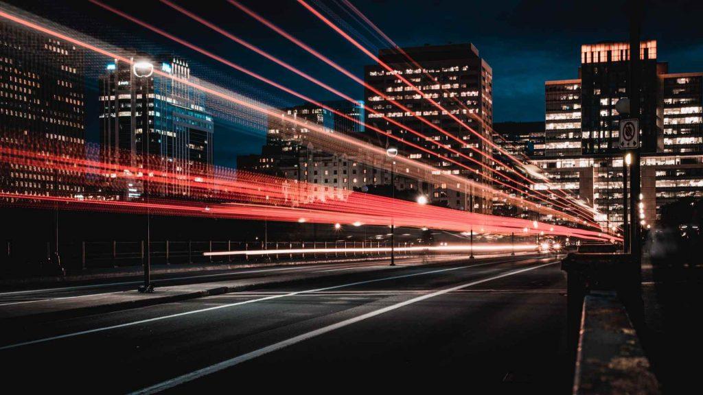 vista noturna de uma avenida entre prédios de uma cidade